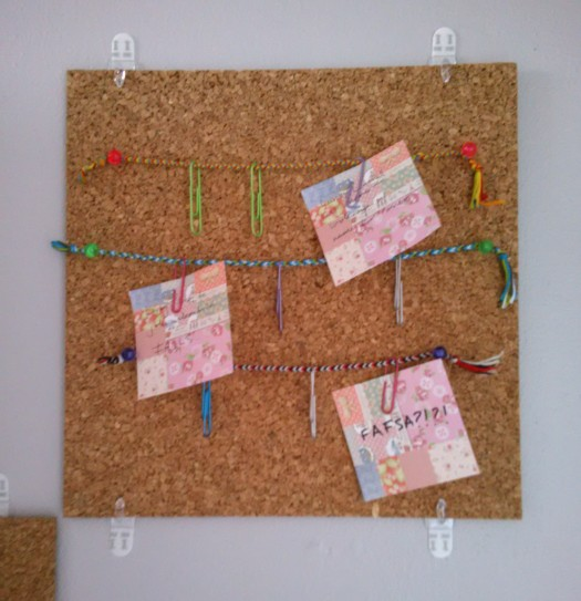 Friendship bracelets pinned to a corkboard to form a clothesline to hang notes